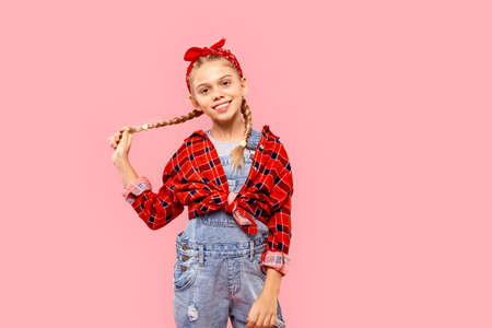 Freestyle. Little girl in bandana on head with braids standing isolated on pink holding braid posing joyful