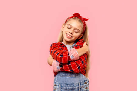 Teenager girl with closed eyes hug herself and smiling nice