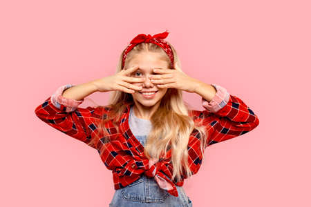 Freestyle. Little girl in bandana on head standing isolated on pink covering eyes smiling playful