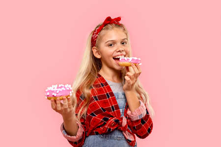 Child girl biting sweet donut and smiling wide