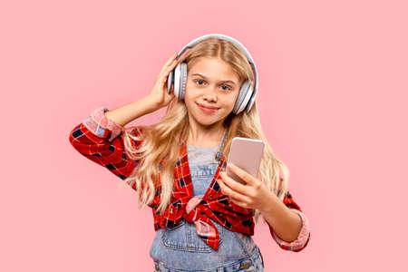Young girl listening music in headphones, using smartphone