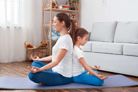Healthy Lifestyle. Mother and daughter in sportswear doing yoga sitting back to back on mat hands in prayer mediating together smiling peaceful Фото со стока