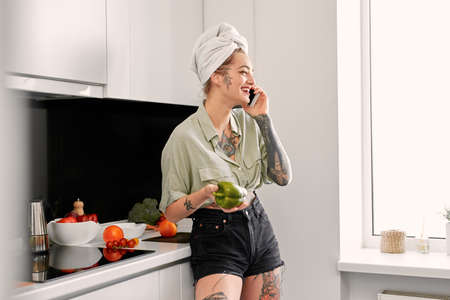 Leisure at Home. Young tattooed woman with towel on head standing at kitchen talking on smartphone with bell pepper while cooking lunch laughing cheerful