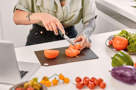 Young adult woman cooking on kitchen, cutting tomato