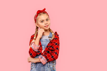 Freestyle. Little girl in bandana on head with braids standing isolated on pink leaning on hand pensive