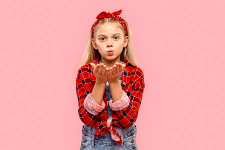 Freestyle. Little girl in bandana on head standing isolated on pink blowing kiss to camera cute