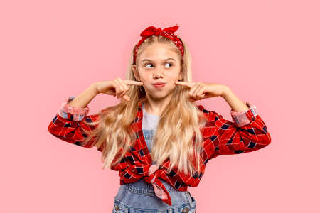 Freestyle. Little girl in bandana on head standing isolated on pink touching cheeks grimacingsmiling playful