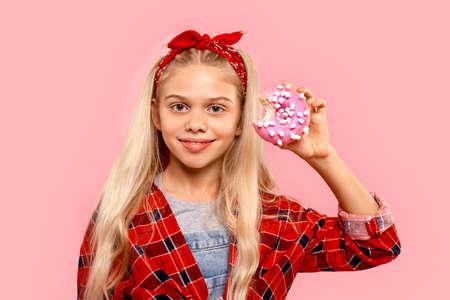 Freestyle. Little girl in bandana on head standing isolated on pink holding bitter sugar glazed donut smiling joyful close-up