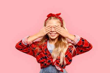 Freestyle. Little girl in bandana on head standing isolated on pink covering eyes laughing cheerful playing hide and seek
