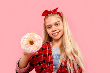 Freestyle. Little girl in bandana on head standing isolated on pink holding sugar glazed donut close-up smiling happy