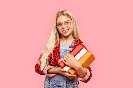 Kid girl holding books in hands and looking at camera