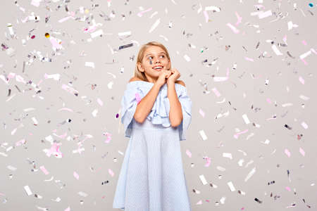 Freestyle. Little girl in dress standing isolated on gray in flying confetti holding hands looking up excited Фото со стока