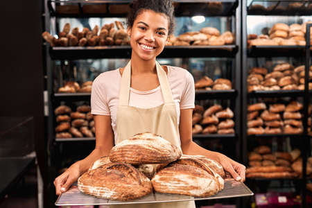 Young adult woman working on bakery factory, holding tray with bread in hands Фото со стока