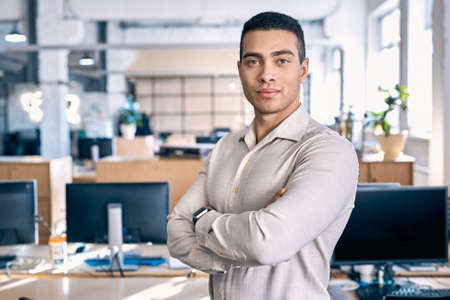 Business Concept. Man in shirt standing close-up on office background crossed arms smiling confident