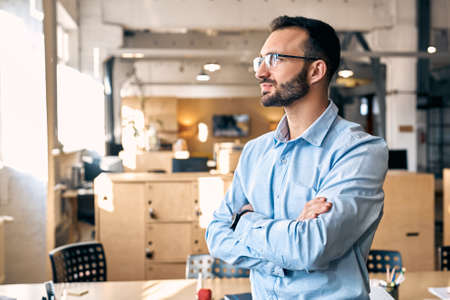 Business Concept. Man in shirt and eyeglasses standing close-up on office background crossed hands looking aside motivated