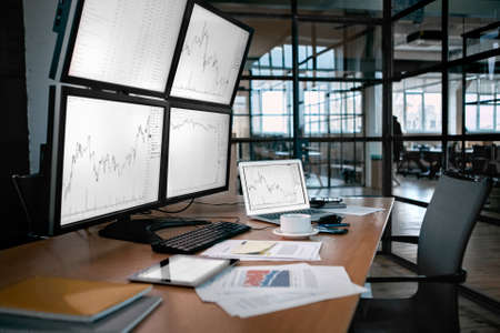 Stock Trading. Trader workplace isolated no people desk in front of monitors with price flow chart Фото со стока