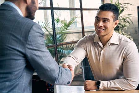 Two businessman making handshake gesture, sitting in office
