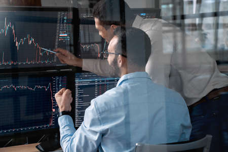 Stock Traiding. Traders sitting at office monitoring price flow analyzing chart talking excited through glass shot