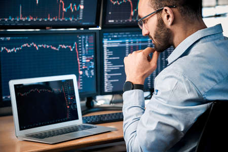 Stock Traiding. Trader sitting at office looking at laptop interpreting candlestick price chart pensive close-up