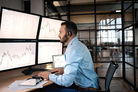 Stock Traiding. Trader sitting at office wearing headset doing online trading training monitoring candlestick price chart concentrated Фото со стока
