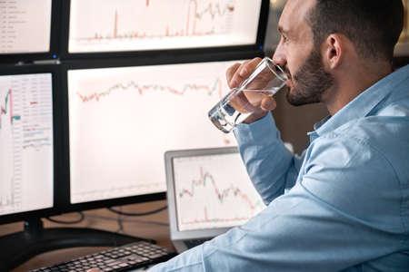 Stock broker drinking water, analyzing global bitcoin price Фото со стока