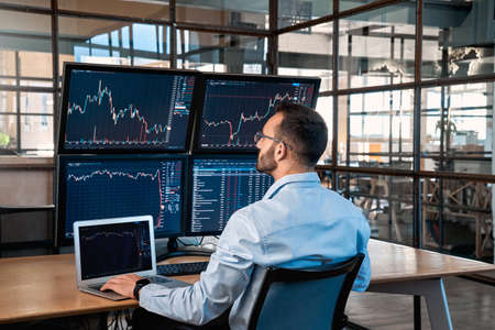 Stock Traiding. Trader sitting at office analyzing price flow on digital screen browsing laptop monitoring market concentrated back view Фото со стока