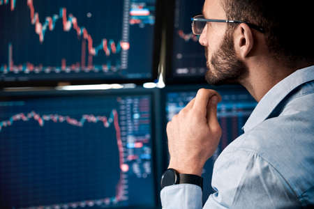 Stock Traiding. Trader sitting at office monitoring market analyzing candle bar price flow on monitors concerned close-up Фото со стока