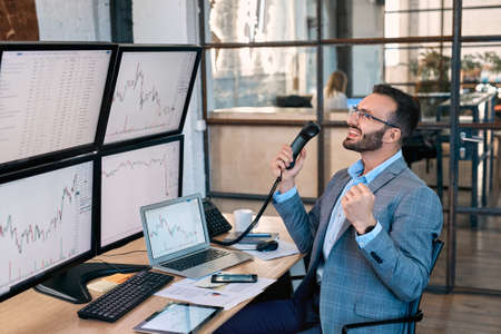 Stock Traiding. Trader sitting at office monitoring market taling on phone doing online trading training laughing cheerful on workplace