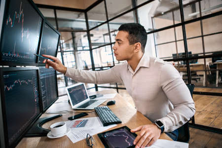 Stock Traiding. Trader sitting at office in front of monitors with data monitoring price flow curious