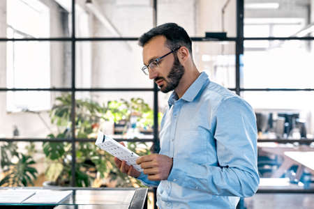 Businessman reading document and standing in office Фото со стока