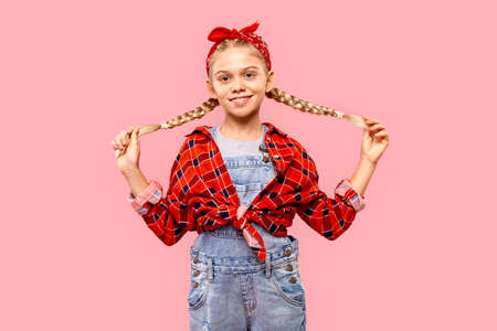 Child girl holding pigtails, smiling cheerful and looking at camera Фото со стока