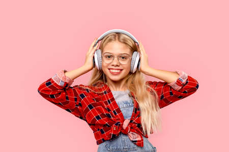 Freestyle. Little girl in eyeglasses and headphones standing isolated on pink listening music smiling cheerful Фото со стока