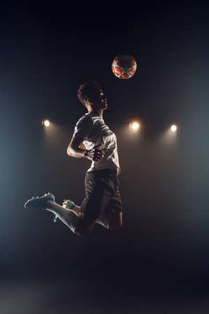 Football. Mulatto guy standing isolated on dark filed jumping misty background smiling happy Фото со стока