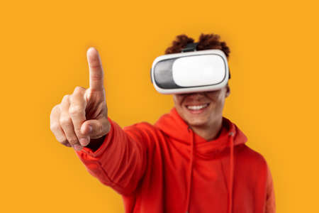 Young adult mulatto in vr glasses pointing with finger Фото со стока