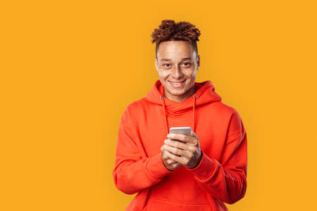 Freestyle. Mulatto freckled guy in hoodie standing isolated on yellow browsing internet on smartphone happy