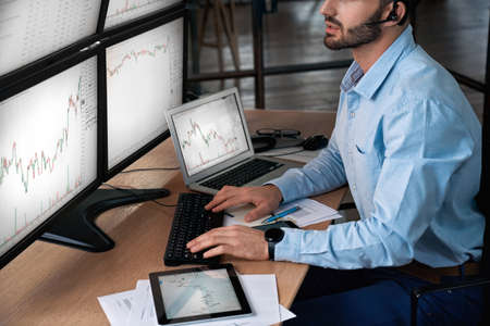 Trader in headset analyzing stat and dynamic on forex charts Фото со стока