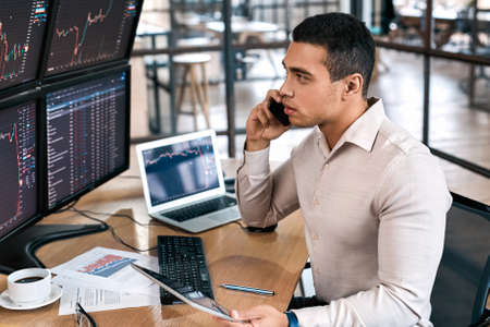 Businessman checking cryptocurrency information data, talking on smartphone