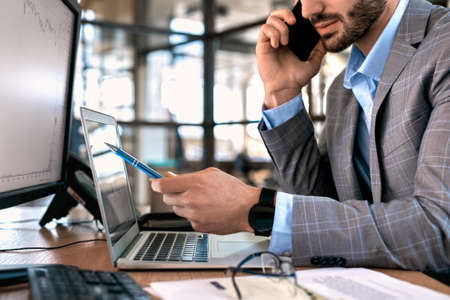 Businessman checking cryptocurrency information and talking on smartphone