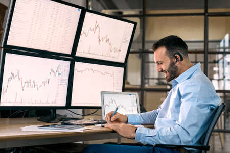 Stock Traiding. Trader wearing headset sitting at office in front of monitors with data chart doing online trading training writing down key points