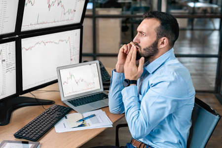 Stock Traiding. Trader sitting in front of monitors with data at office talking on phone doing online trading training discussing business strategy concerned
