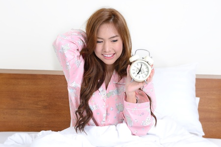 Pretty girl wake up in the morning with alarm clock in her hand  photo