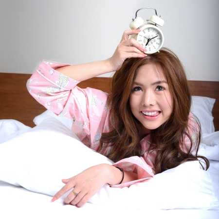 Pretty girl lying on the bed with alarmclock  photo