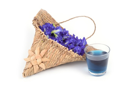 A glass of butterfly pea juice and some butterfly pea in small hanging wicker basket on white background  photo