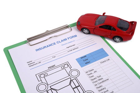 Insurance claim form on cilpboard with a red car model