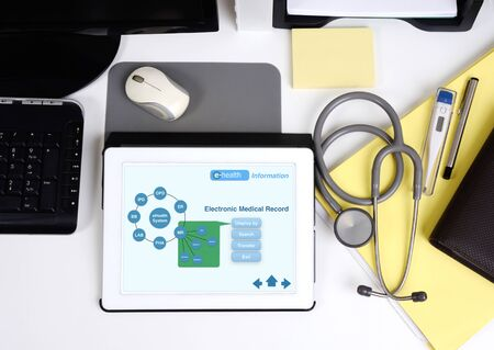 Top view of doctor working desk and tablet shown the electronic information.