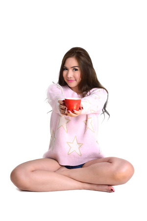 put forward: Cute long hair woman in pink sweater sit on the floor and put red coffee cup in her two hands forward on white background.