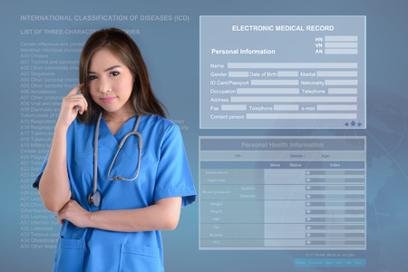 Female doctor in blue uniform thinking about her work in front of electronic medical record background. Banco de Imagens