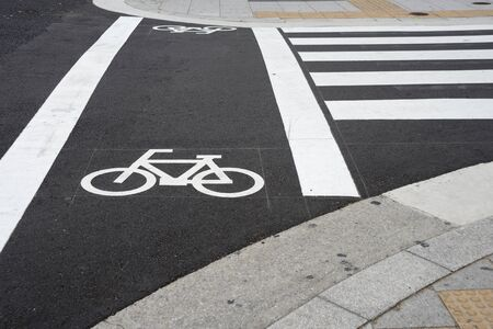 lane lines: Bicycle sign beside crosswalk on the road in city for bike path.