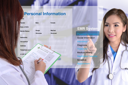medical person: Female doctor show how to use electronic medical record while another one checking patient information by hand.
