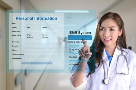 paciente: Mujer médico con sistema de registro médico electrónico para buscar información del paciente. Foto de archivo